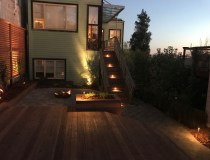 Backyard Landscape Project: After, at dawn: Framed redwood lattice screens the neighbor's wall, illuminated steps lead to the house while the natural gas firepit provides additional beauty to the landscape