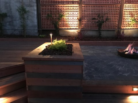 Backyard Landscape Project: Planter boxes made of new redwood with reclaimed onsite cedar, hold decorative plants and upright lighting