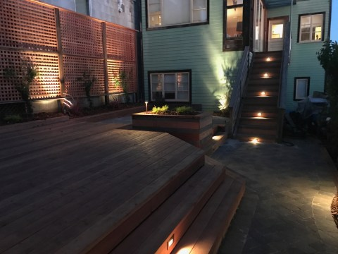 Backyard Landscape Project: View of deck, lattice and stair lighting from the path