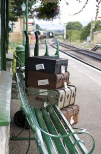 train platform with old fashioned luggage and bench
