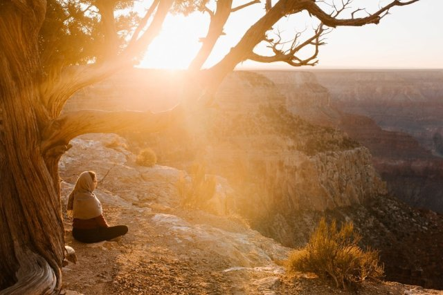 A person meditating at sunset at Hopi Point on the South Rim of the Grand Canyon by photographer Tami Keehn.