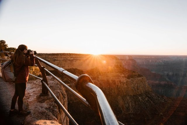 A woman photographing the Sunset at Hopi Point on the South Rim of the Grand Canyon by photographer Tami Keehn.