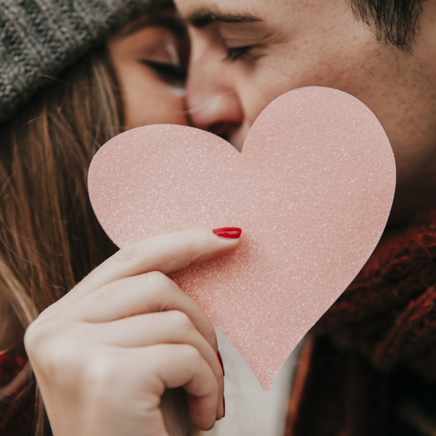 couple-kissing-and-holding-heart_23-2147736074