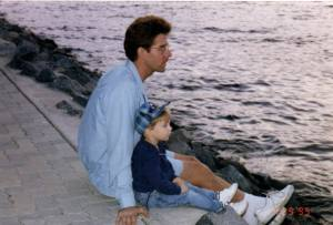 Father and son sitting by the water.