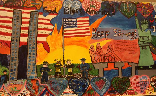 Mural of children's drawing of 9/11 with flag, US map, firefighters, & twin towers &