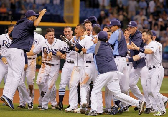 The Rays mob Yunel Escobar after his single over Tigers centerfielder Austin Jackson's head drives in Sam Fuld with the winner in the 10th. (Photo courtesy of Daniel Wallace/Tampa Bay Times)