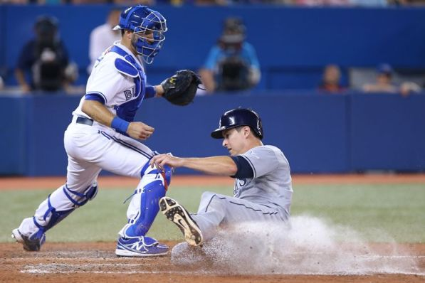 The Rays' Kelly Johnson slides home with the go-ahead run in the eighth inning in front of Jays catcher J.P. Arencibia. (Photo courtesy of Getty Images)
