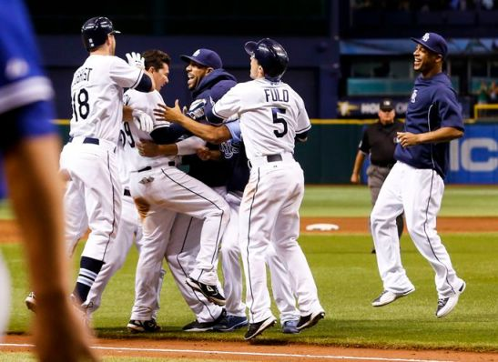 Rays players converge on catcher Jose Lobaton, second from left, after his ninth-inning triple delivers another walkoff victory. (Photo courtesy of Will Vragovic/Times)
