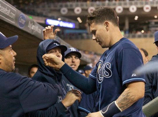 Jose Lobaton is greeted in the dugout after scoring on Evan Longoria's two-out double in the third inning. (AP photo)