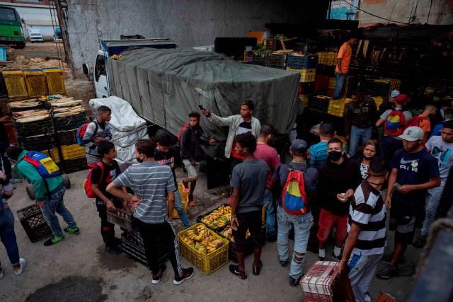 Personas que se dedican a obtener productos mediante trueque con plátanos trabajan en un galpón ubicado en Catia, el 18 de enero de 2021 en Caracas (Venezuela). EFE/RAYNER PEÑA R