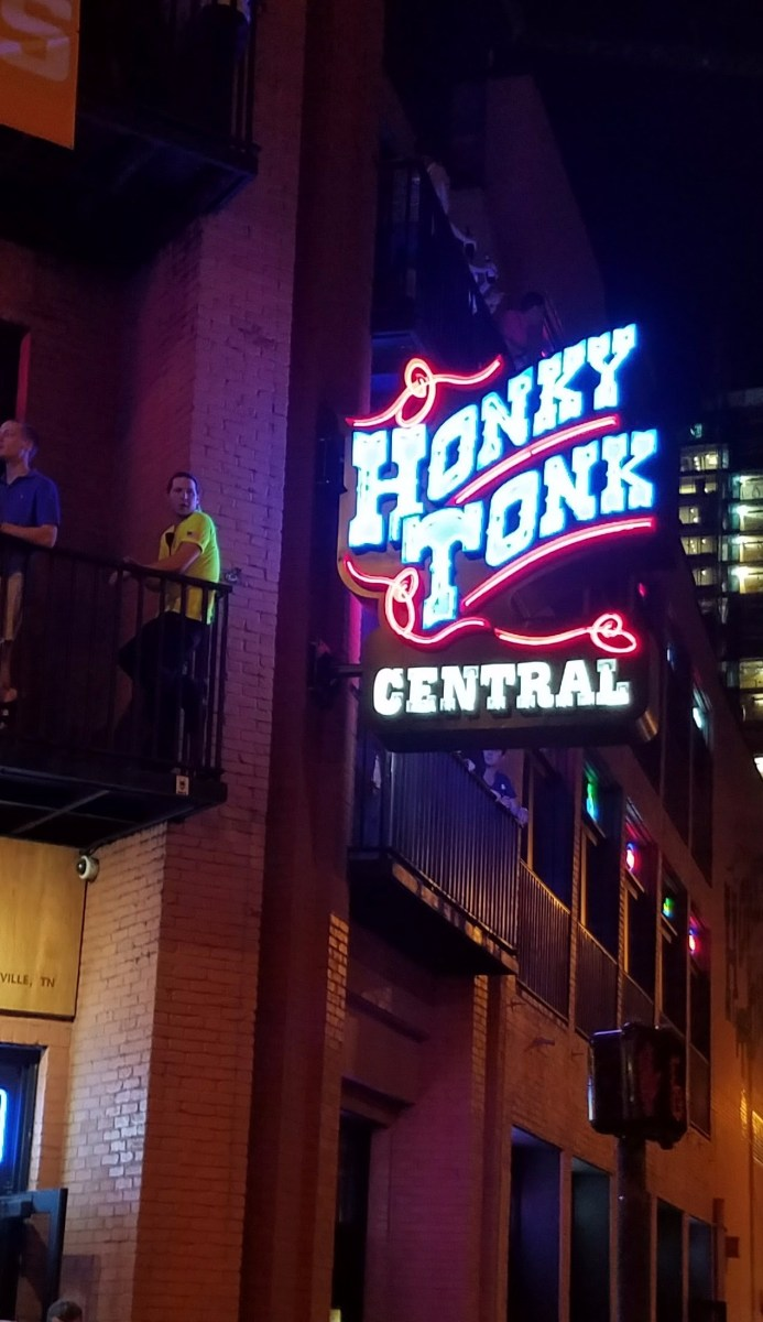 honky tonk central lit up sign outside of the building in nashville tn