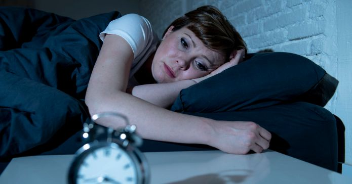 A person, unable to sleep, staring at the clock. Sleep deprivation provides misery to many.