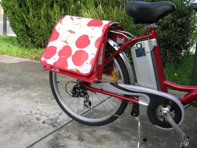 red electric bike sporting panniers with red apple pattern