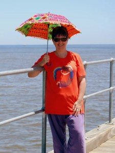 Yvette J on the jetty, she is smiling and wearing Rainbow Lady tshirt design on orange shirt, and holding a rainbow umbrella.