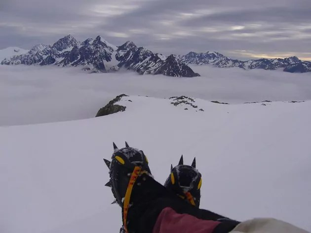 spikey shoe-d feet, crossed, with an outlook over NZ snowy mountain, Mt Cook