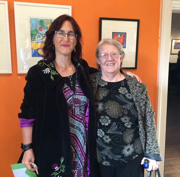 Tangerine Meg and author Susan Fitzgerald standing in fromt of orange wall displaying framed brightly coloured lino prints and watercolours
