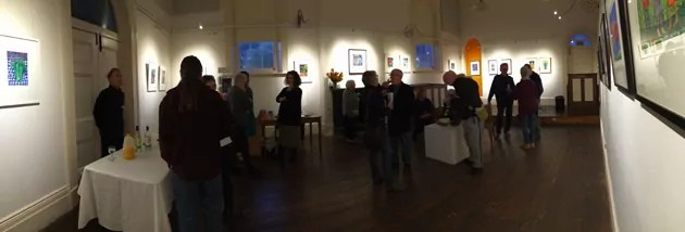 a panoramic shot around a large room, with folk almost silhouetted attending an exhibition launch.