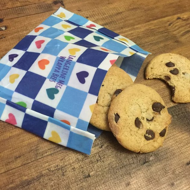 chocolate chip cookies spilling out of a checkered reusable wax food wrap fashioned into a pocket