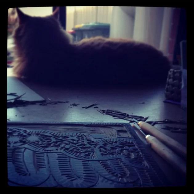 Orange Cat beside a carved lino print in progress