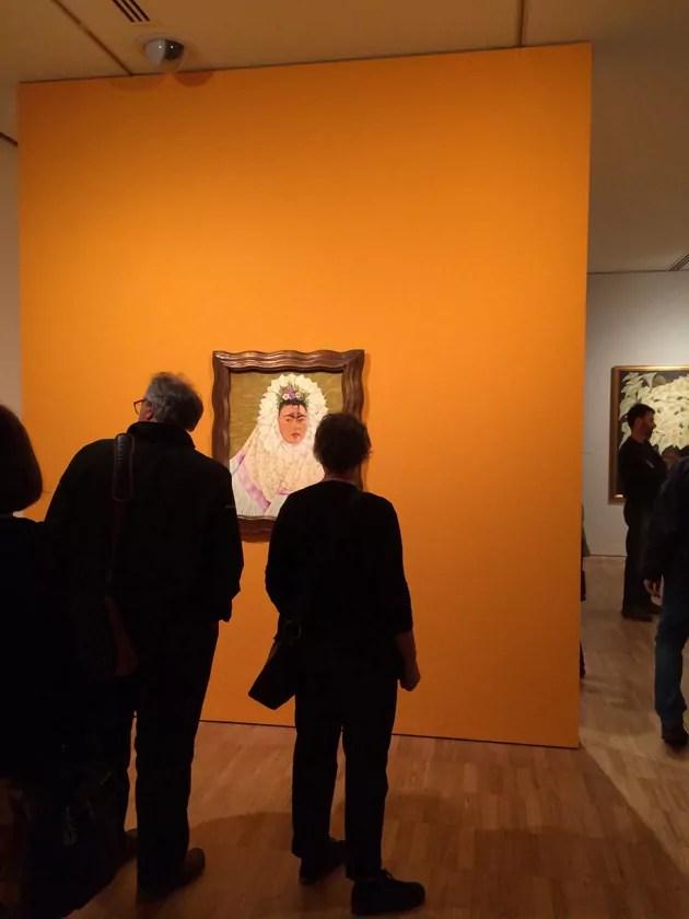 Backs of people viewing Frida Kahlo painting on orange wall.