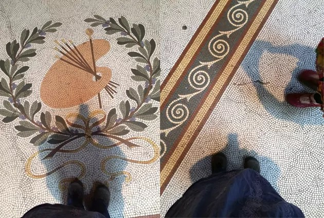Feet standing on mosaic floor. The floor has small tiles making a curved repeated pattern and featuring an artist's palette surrounded by an olive branch design.