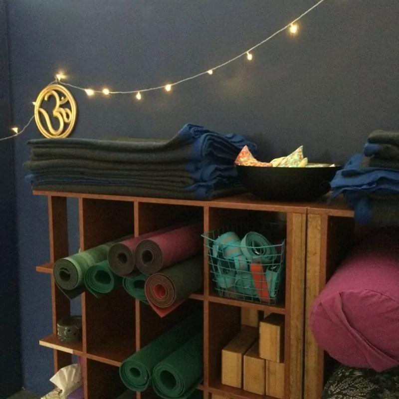 bolsters, blocks and other yoga equipment neatly stored under the OM sign and fairy lights