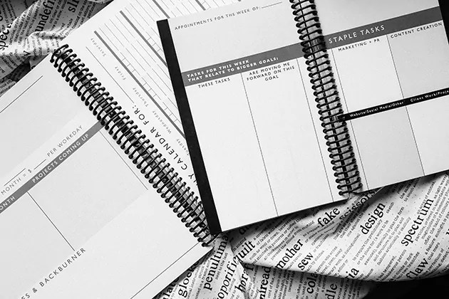 Black and white photo of a large and a small Freelancer Planner opened up so you can see the page layouts.