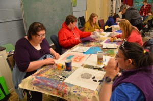 A photograph of a group of people seated at a table doing a stencil workshop