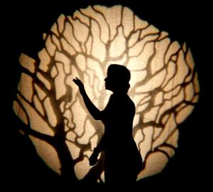 A square image of a silhouetted figure on a peach coloured background. The figure sits in the center of the peach coloured circle reaching up with their left hand. They look off into the upper left corner of the image, standing with their back strait. The circle behind them is divided up with the silhouette of branches growing from the bottom of the image and cutting up through the piece.
