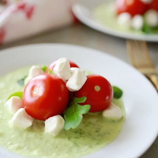 Caprese salad appetizer with fresh Campari tomatoes, spring greens, and mozzarella pearls; all in a vibrant sweet basil foam.