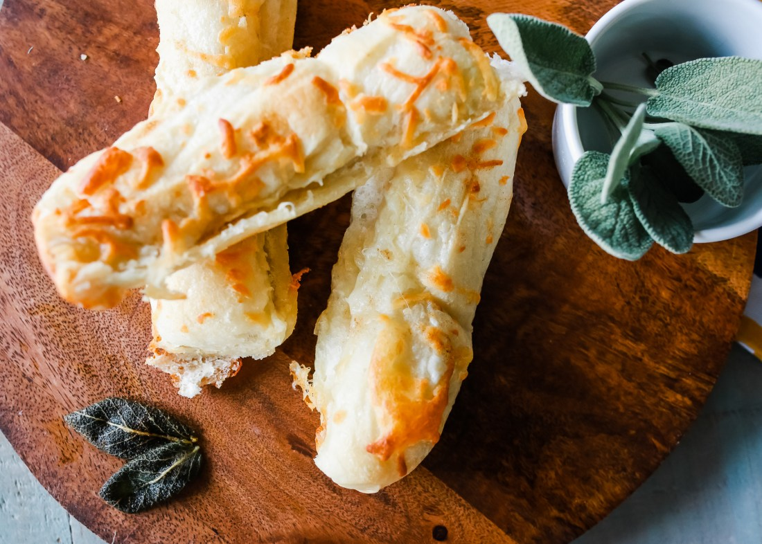 Cheesy breadsticks with a subtle delicious brown butter and sage flavoring. Easy breadsticks to make using frozen real yeast roll dough.