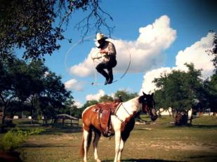 A cowboy does rope tricks on horseback