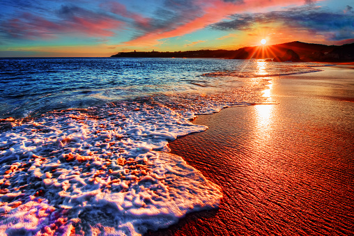 Brilliant vacation beach sunrise with colorful sand and distant cliffs