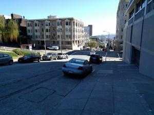 Looking down a steep sidewalk toward Sacramento and California cross streets.