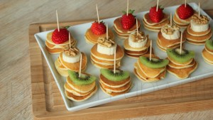 A tray of mini pancake canapes, each topped with a piece of fruit and a toothpick