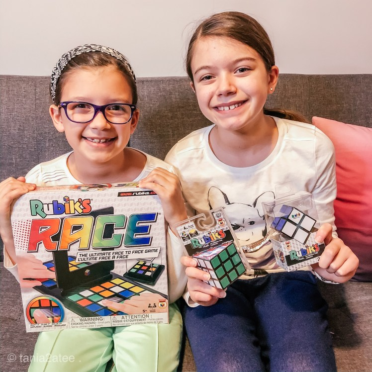 two girls holding Rubik's Cubes and Rubik's Race game