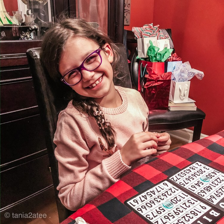 little girl wearing glassing playing bingo