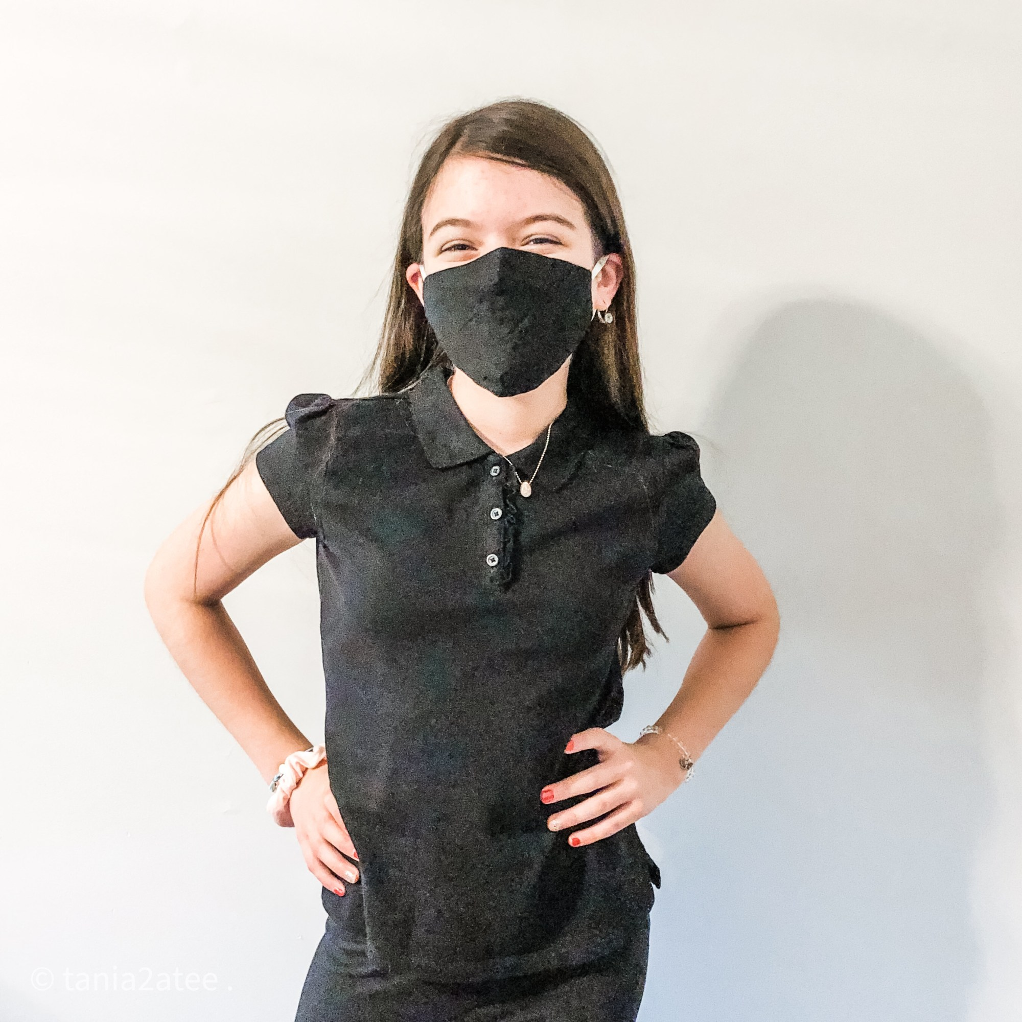 girl posing for camera wearing black top and pants and black face mask