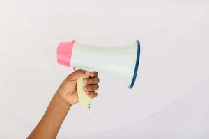Hand holding a pink and white megaphone