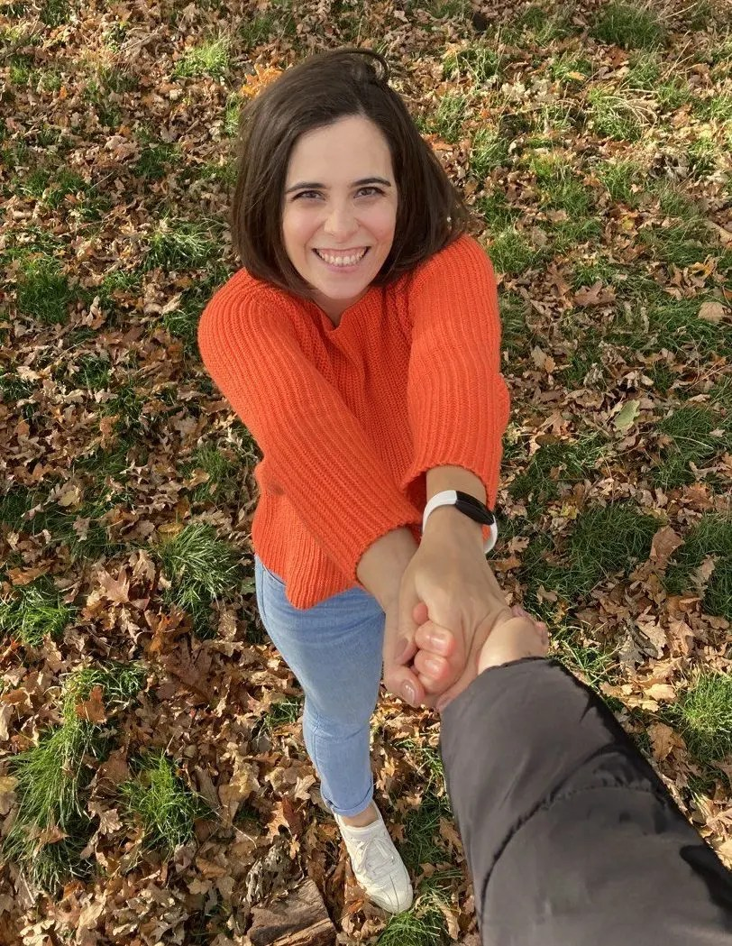 Tania, with a smiley face, holding another person's hand with both her hands. Tania is wearing an orange top and jeans. Photo is taken from above so the background is of the autumn leaves in the park.