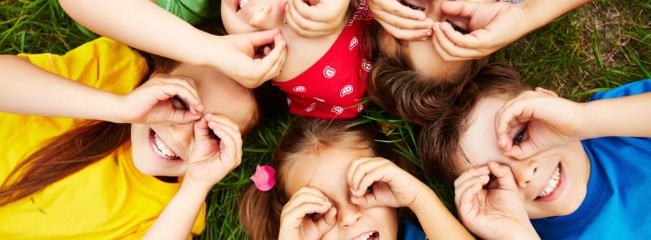 Des enfants couchés dans l'herbe, les mains en lunettes autour des yeux.