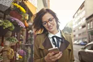 woman beside flower shop using smartphone