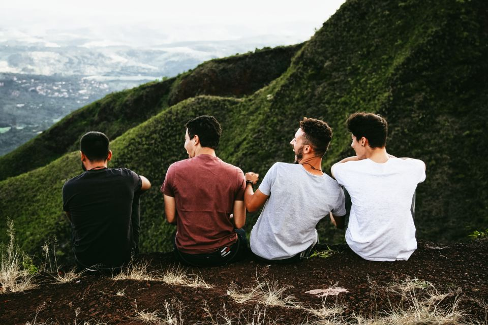 4 young men sitting beside a mountain