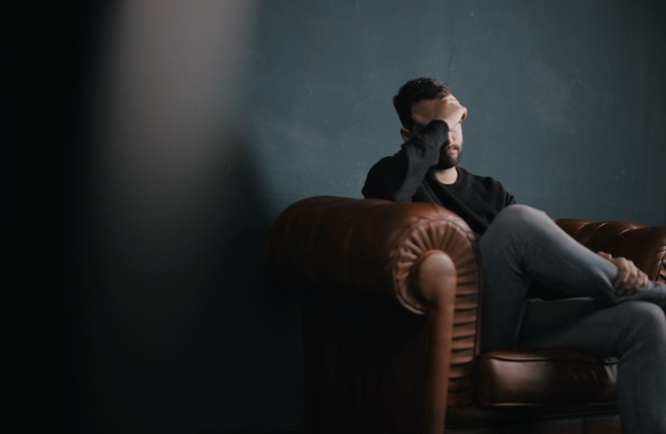 a man sitting on a sofa with his head in his hand