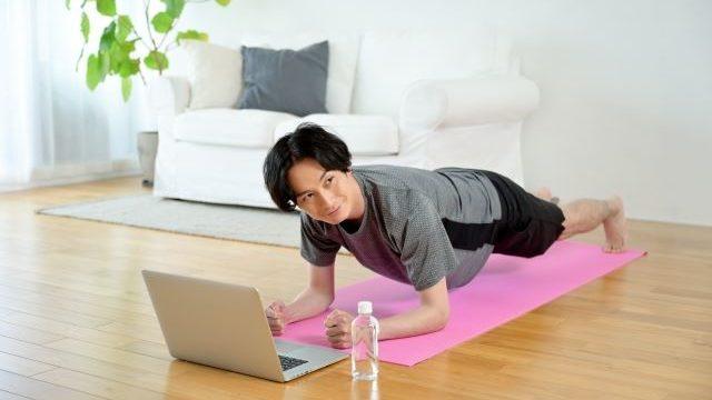 運動しながらパソコンを見ている男性