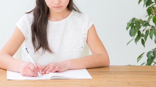 新聞コラムを書き写す女性