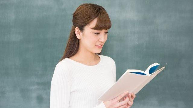 教科書を読んでいる教師