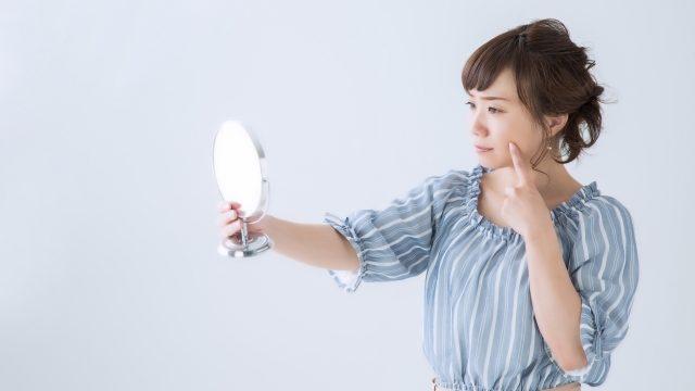 鏡を持って、肌荒れを気にする女性