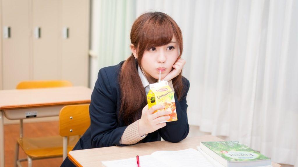 授業に集中しないでジュースを飲む女子高生
