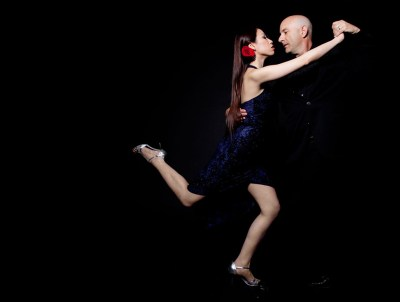 Passionate couple dancing the tango on black background